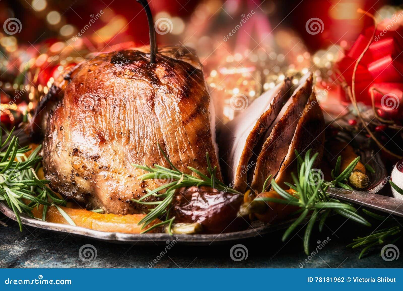 Weihnachten schnitt gebratenen Schinken auf dinning Tabelle mit festlicher Feiertagsdekoration, Seitenansicht