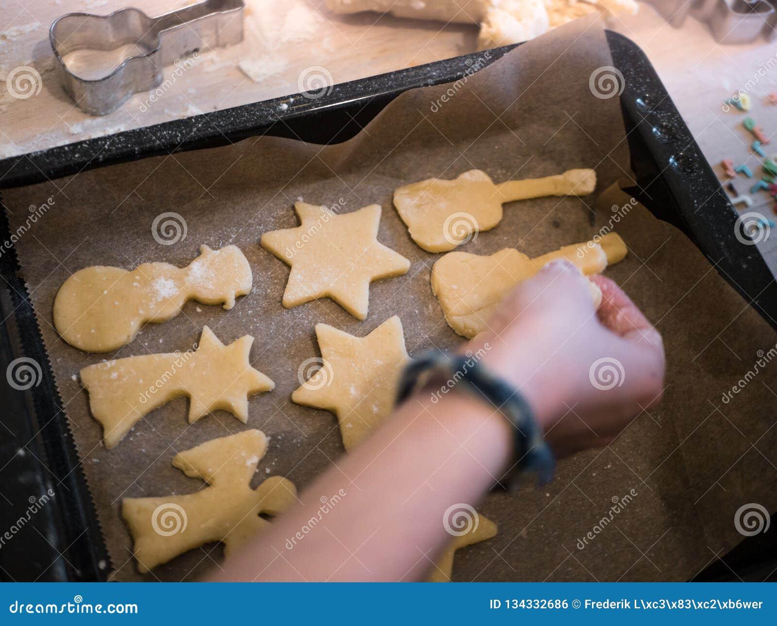 Weihnachtsbäckerei: Wenig Mädchen, das verschiedene Formen des Plätzchenteigs auf ein Backblech setzt