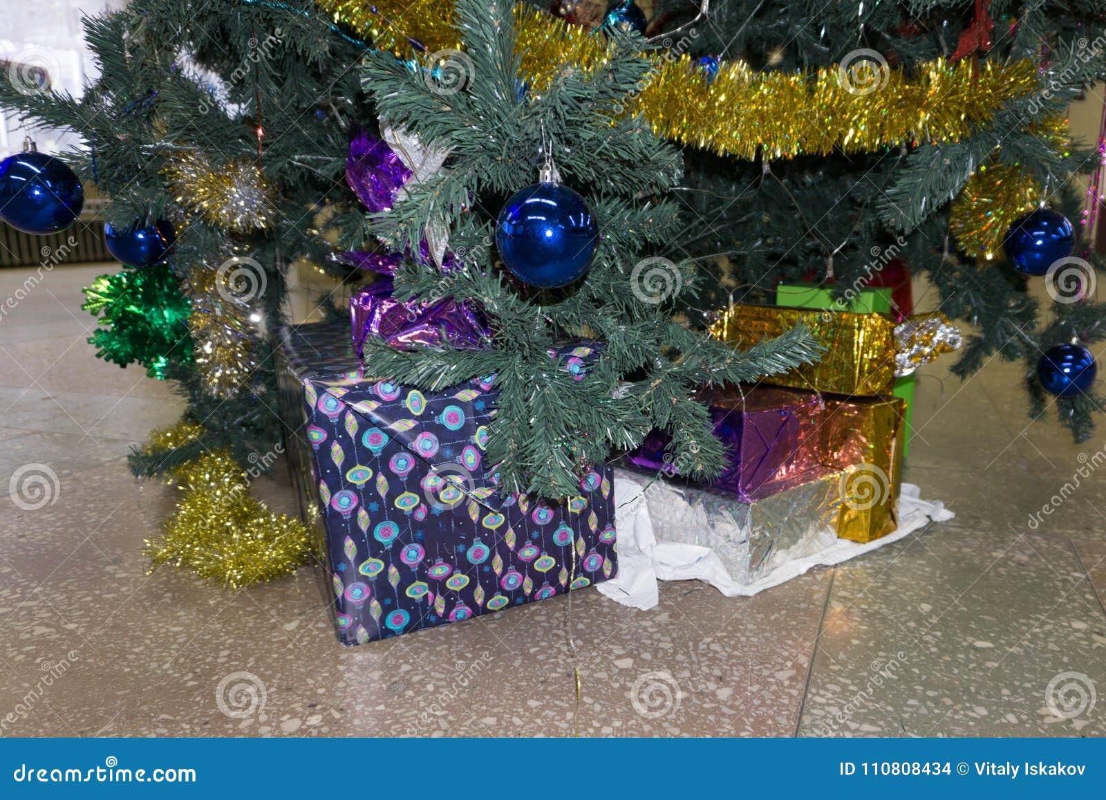 Weihnachtsbaum mit hölzernen rustikalen Dekorationen und Geschenken unter ihm im Dachbodeninnenraum
