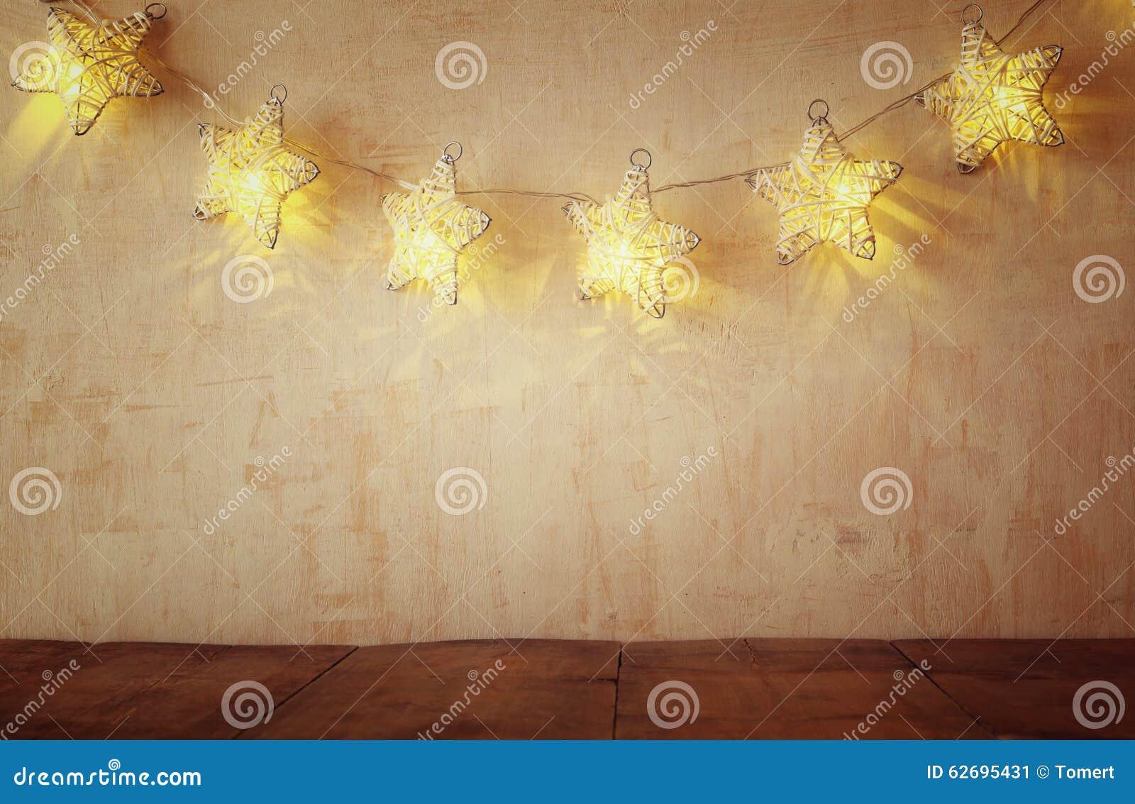 Weihnachtsbeleuchtet warme Goldgirlande auf hölzernem rustikalem Hintergrund