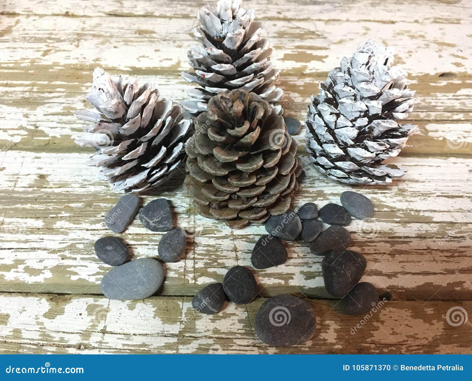 Weihnachtsdekoration mit Kiefernkegeln färbte die weißen und roten Steine auf Holz