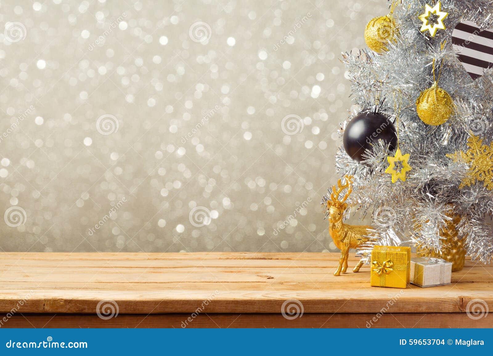Weihnachtsfeiertagshintergrund mit Weihnachtsbaum und Dekorationen auf Holztisch Schwarze, goldene und silberne Verzierungen