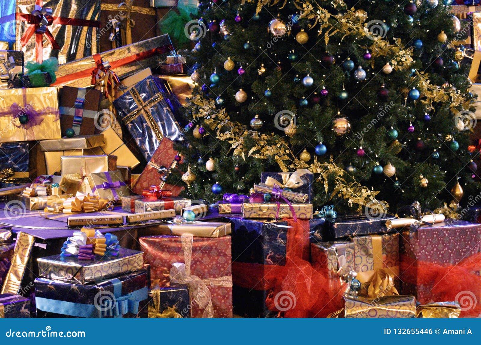 Weihnachtsgeschenke ringsum die Basis eines Weihnachtsbaums