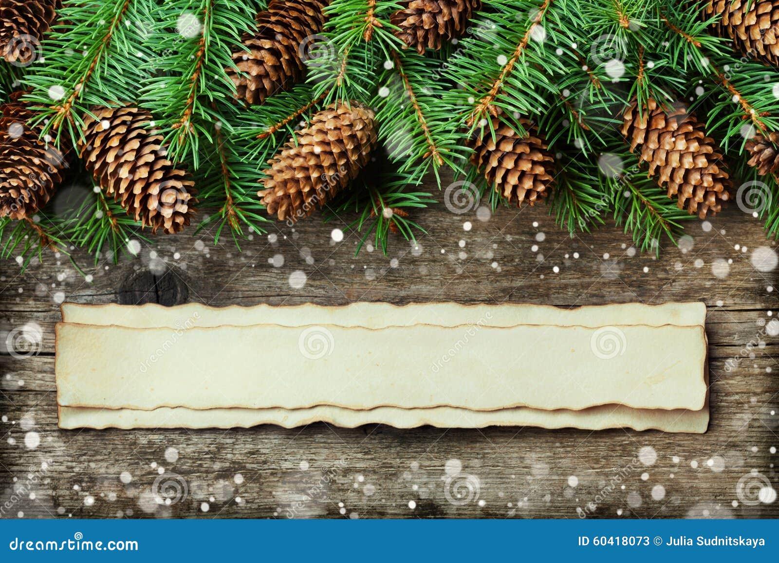 Weihnachtshintergrund des Tannenbaums und des Nadelbaumkegels auf hölzernem Brett der alten Weinlese, fantastischer Schneeeffekt