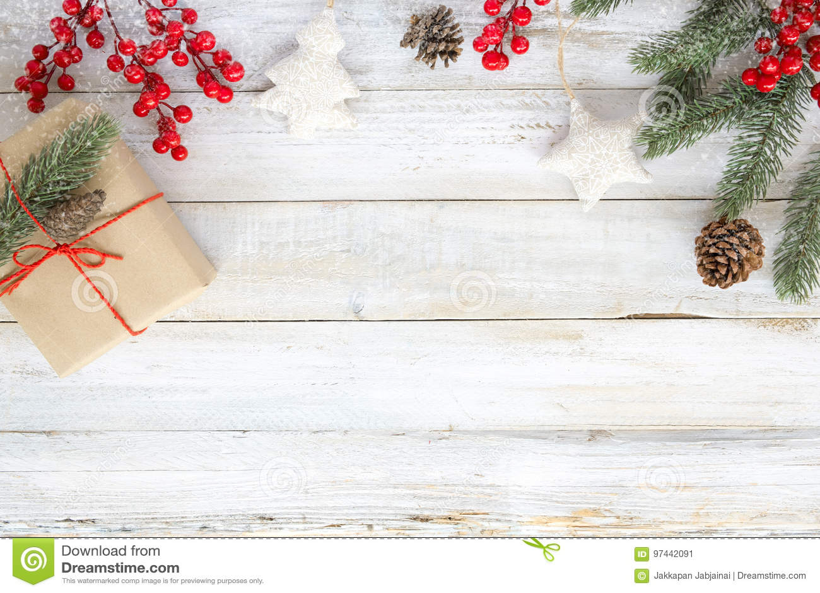 Weihnachtshintergrund mit Dekorationen und handgemachten Geschenkboxen auf weißem hölzernem Brett mit Schneeflocke