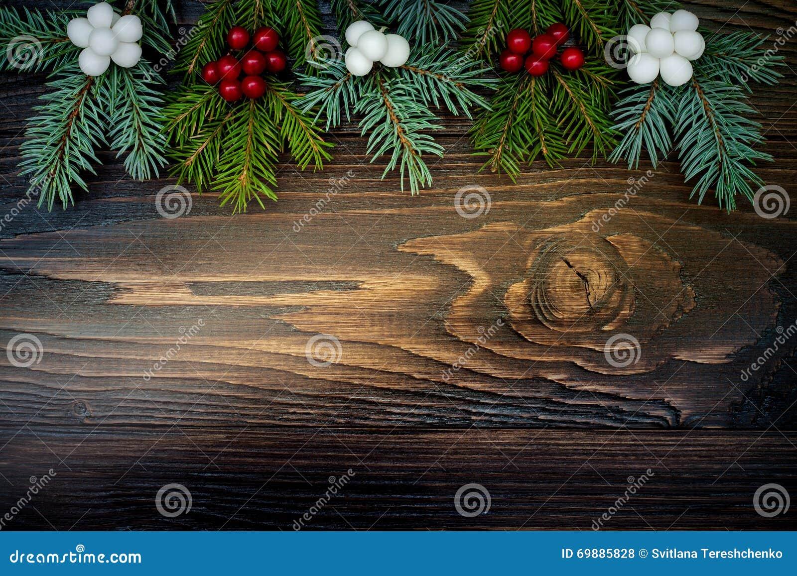 Weihnachtshintergrund mit Tannenzweigen und Beeren auf hölzernem Brett des Schmutzes Kopieren Sie Platz