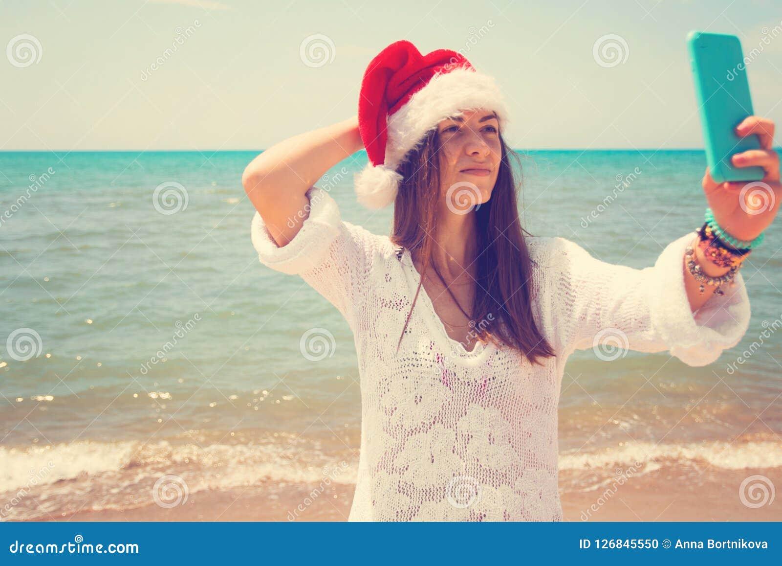 Weihnachtsjunge lächelnde Frau in rotem Sankt-Hut, der Bildselbstporträt auf Smartphone am Strand über Seehintergrund nimmt geton