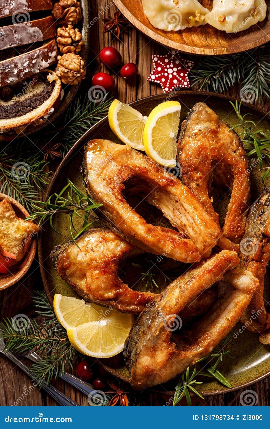 Weihnachtskarpfen, gebratene Karpfenfischscheiben auf einer keramischen Platte, Abschluss oben Traditioneller Weihnachtsabendstel