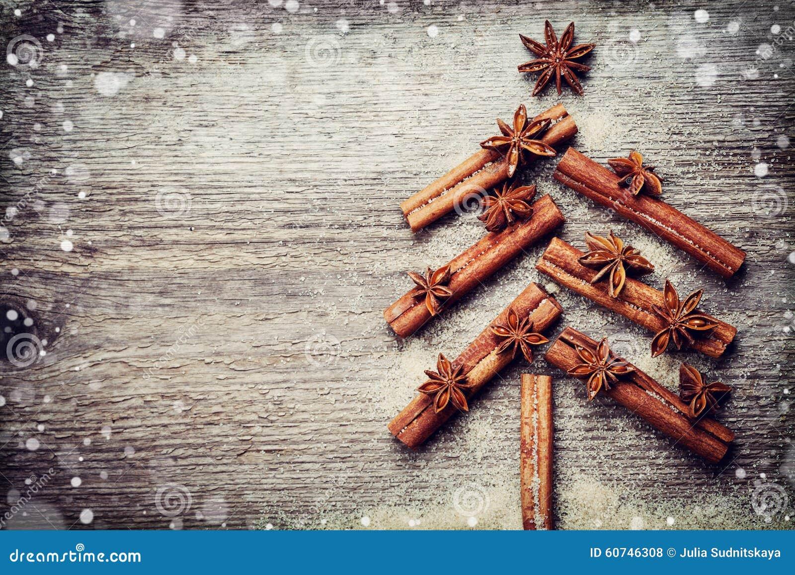 Weihnachtskarte mit dem Weihnachtstannenbaum gemacht von den Gewürzzimtstangen, vom Anisstern und vom Rohrzucker auf rustikalem h