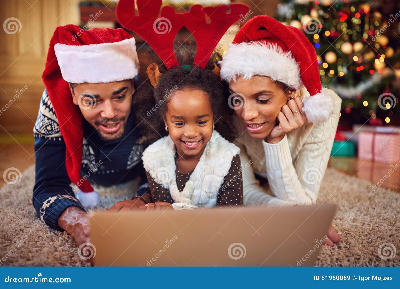 Weihnachtskaufende on-line-Familie, die auf Computer surft
