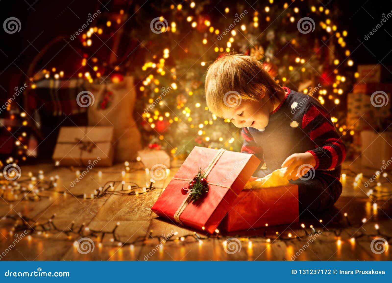 Weihnachtskinderoffenes anwesendes Geschenk, glückliches Baby, das Kasten schaut