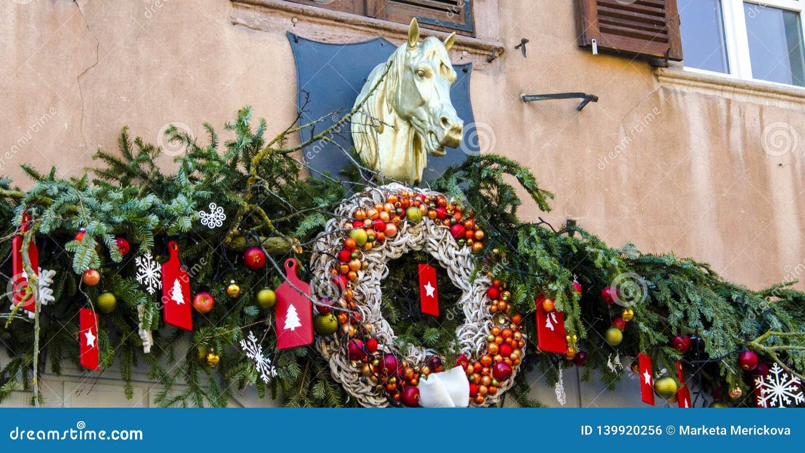 Weihnachtskranz und -dekorationen auf Fassade mit Skulptur des Pferds
