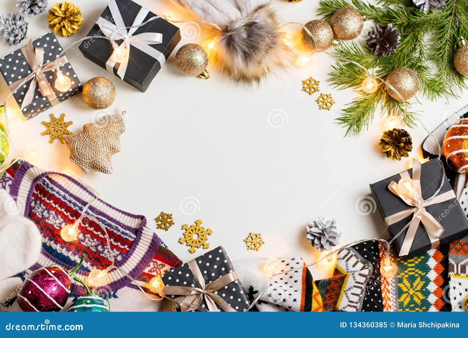 Weihnachtsstimmungszusammensetzung mit Weihnachtsstrickjacke, -hut, -geschenken und -lichtern Flache Lage des Winterkonzeptes, Dr