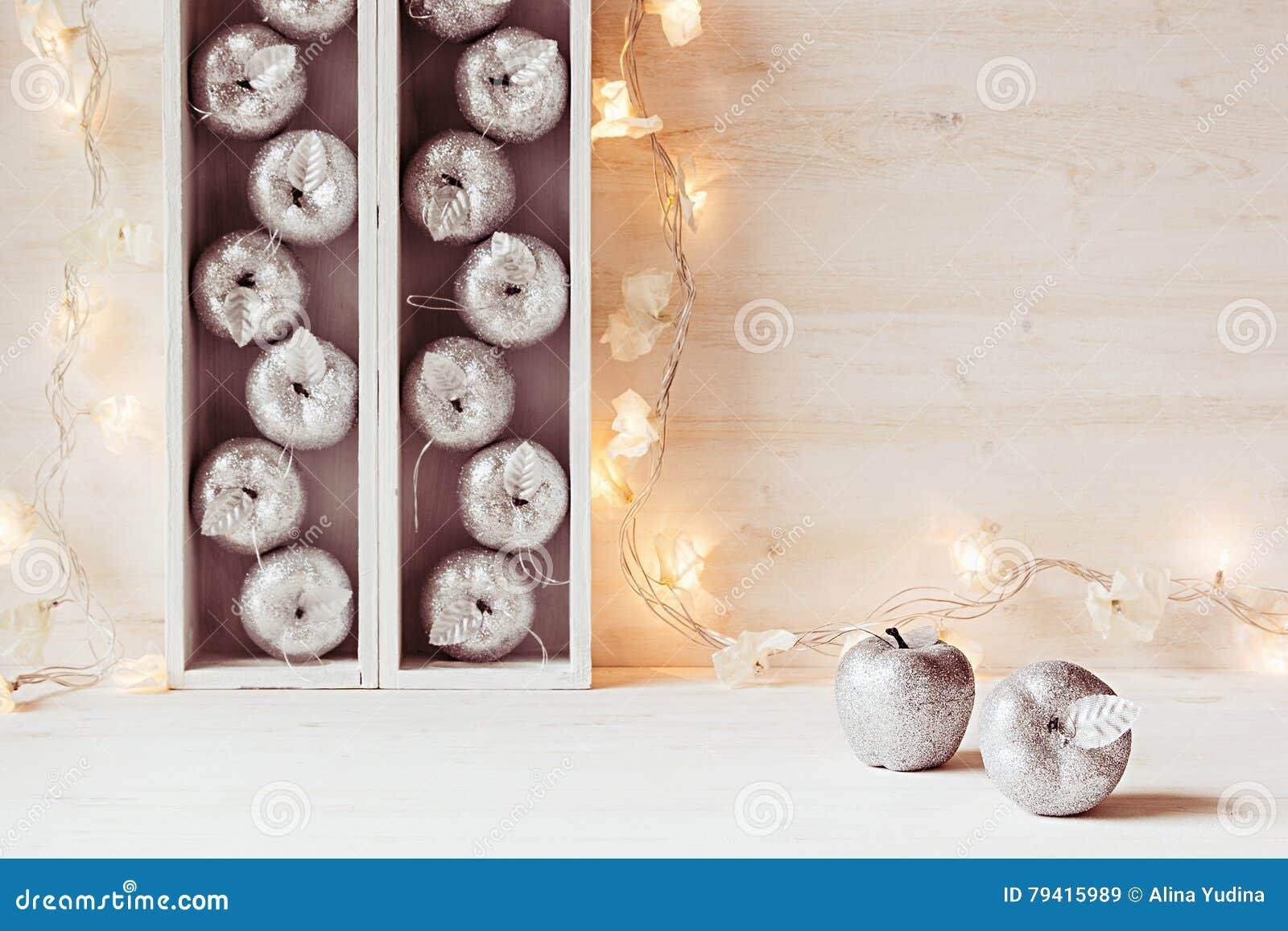 Weihnachtsweicher Hauptdekor von silbernen Äpfeln und von Lichtern, die in den Kästen auf einem hölzernen weißen Hintergrund bren