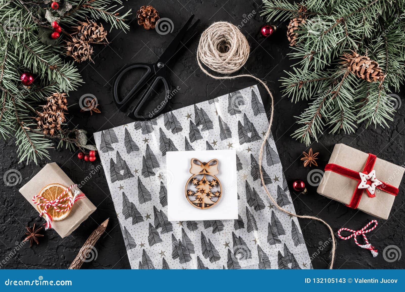 Weihnachtszusammensetzung mit Buchstaben, einwickelndes Weihnachten, Tannenzweige, Geschenke, Kiefernkegel, rote Dekorationen, Sc