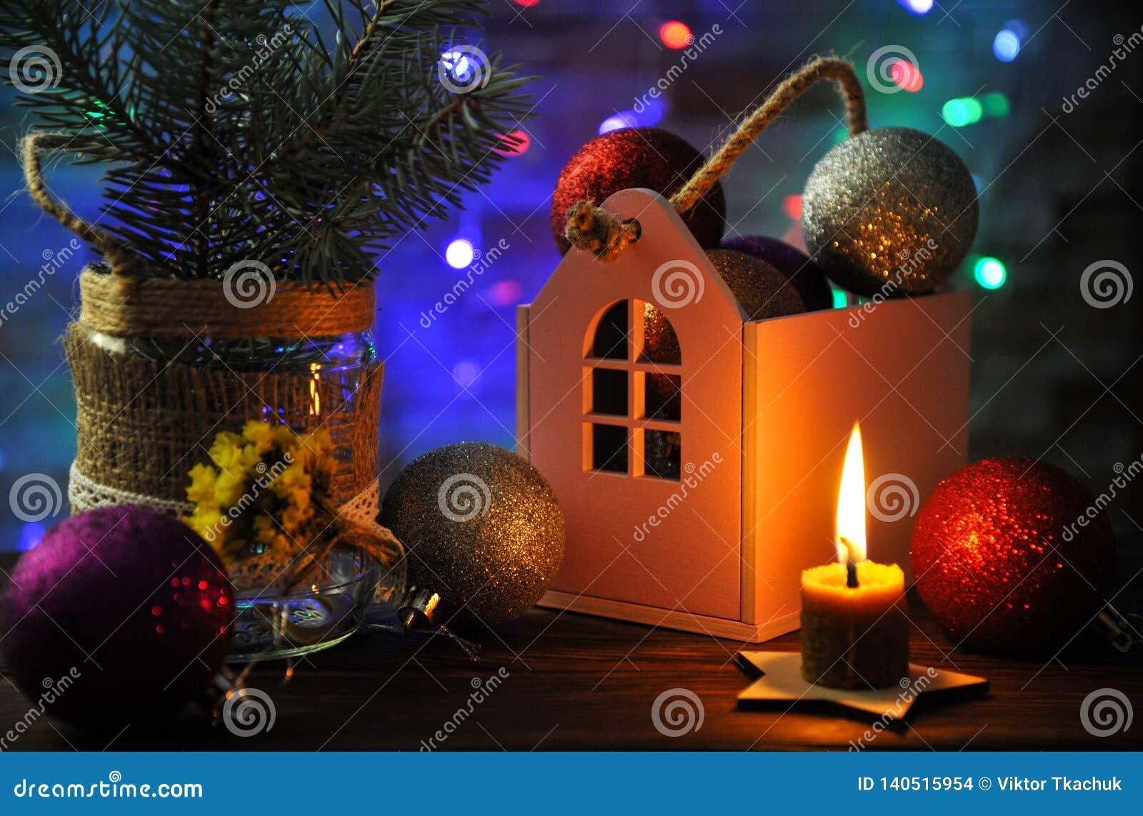 Weihnachtszusammensetzung mit einer brennenden Kerze, einem Haus und Weihnachtsdekorationen auf einer Tabelle