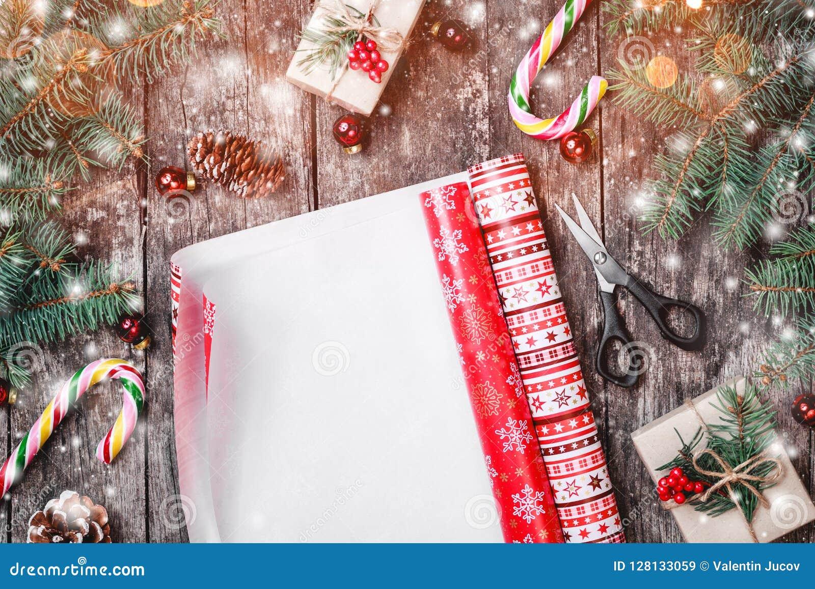 Weihnachtszusammensetzung mit einwickelndem Weihnachten, Tannenzweige, Geschenke, Kiefernkegel, rote Dekorationen auf hölzernem H