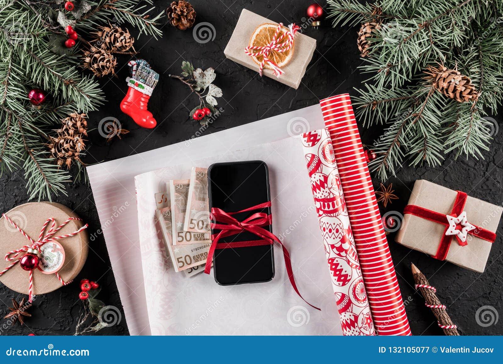 Weihnachtszusammensetzung mit Handy, Geld, einwickelndes Weihnachten, Tannenzweige, Geschenke, rote Dekorationen auf dunklem Hint