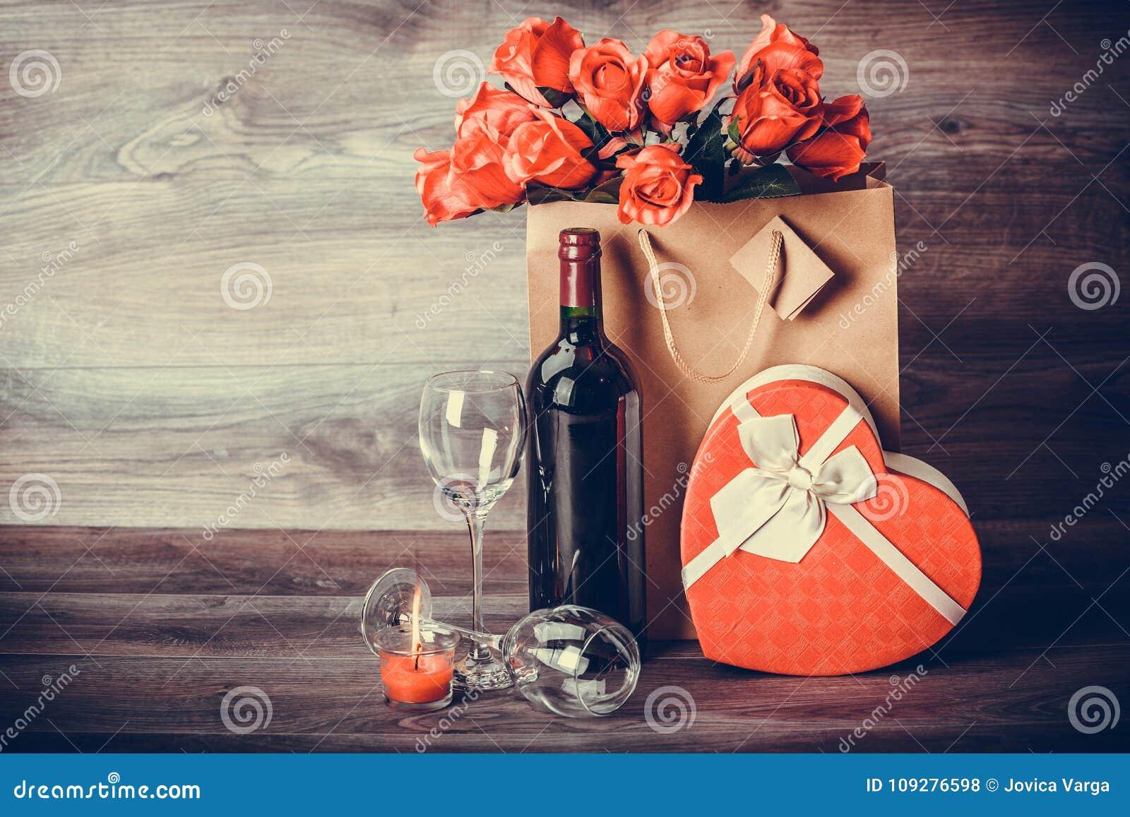 Wein, rosafarben und Herz als Geschenk auf dem Tisch