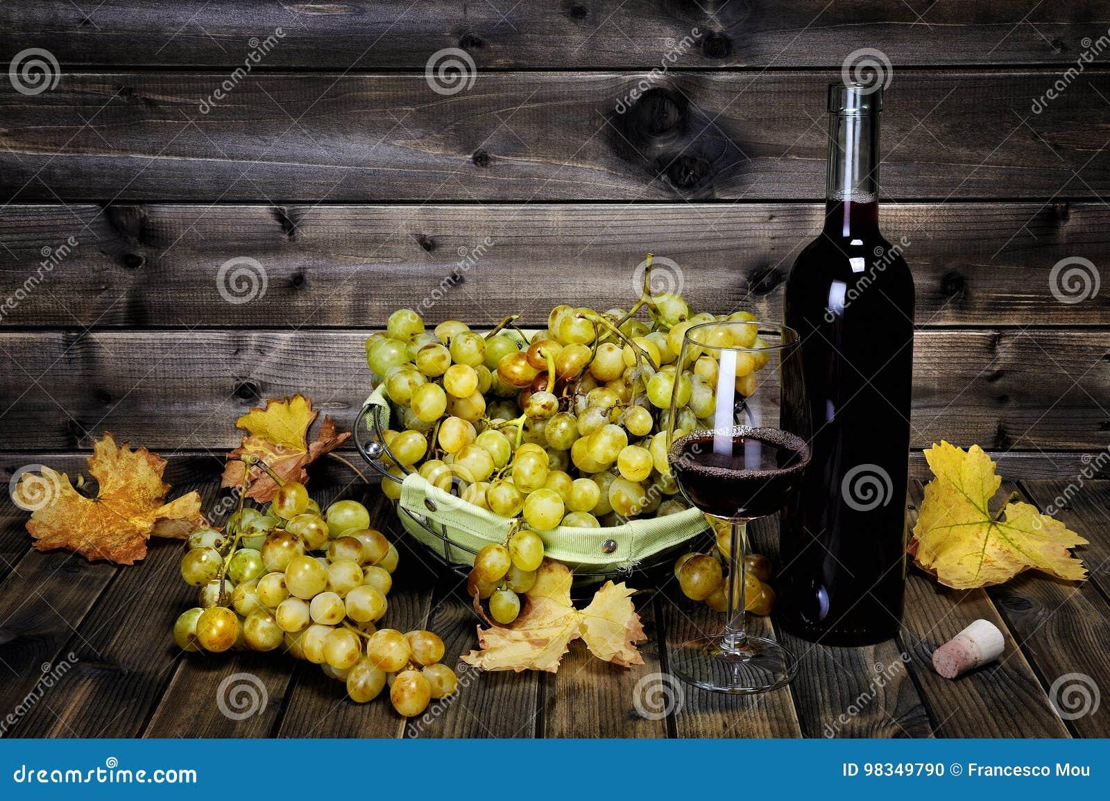 Weinglas und neues Bündel weiße Trauben auf antikem hölzernem BAC