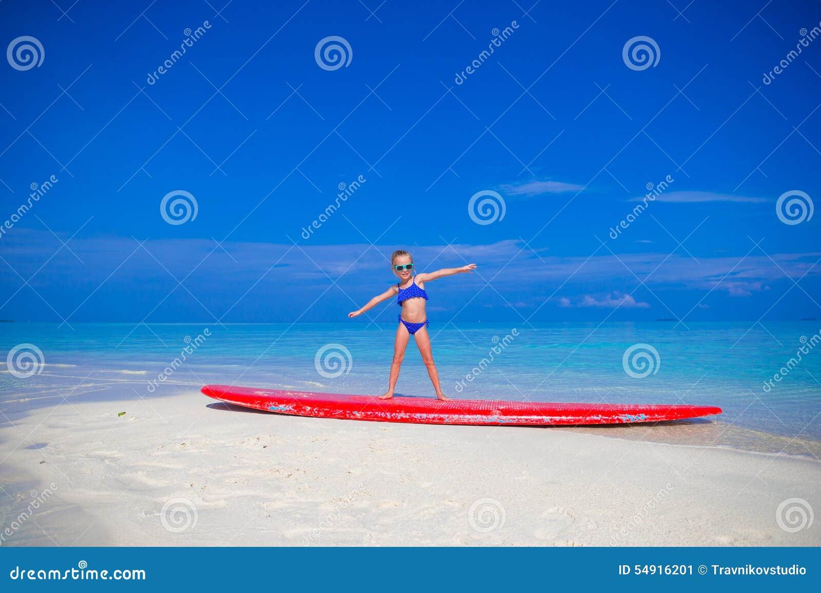 Weinig aanbiddelijk meisje op een surfplank in