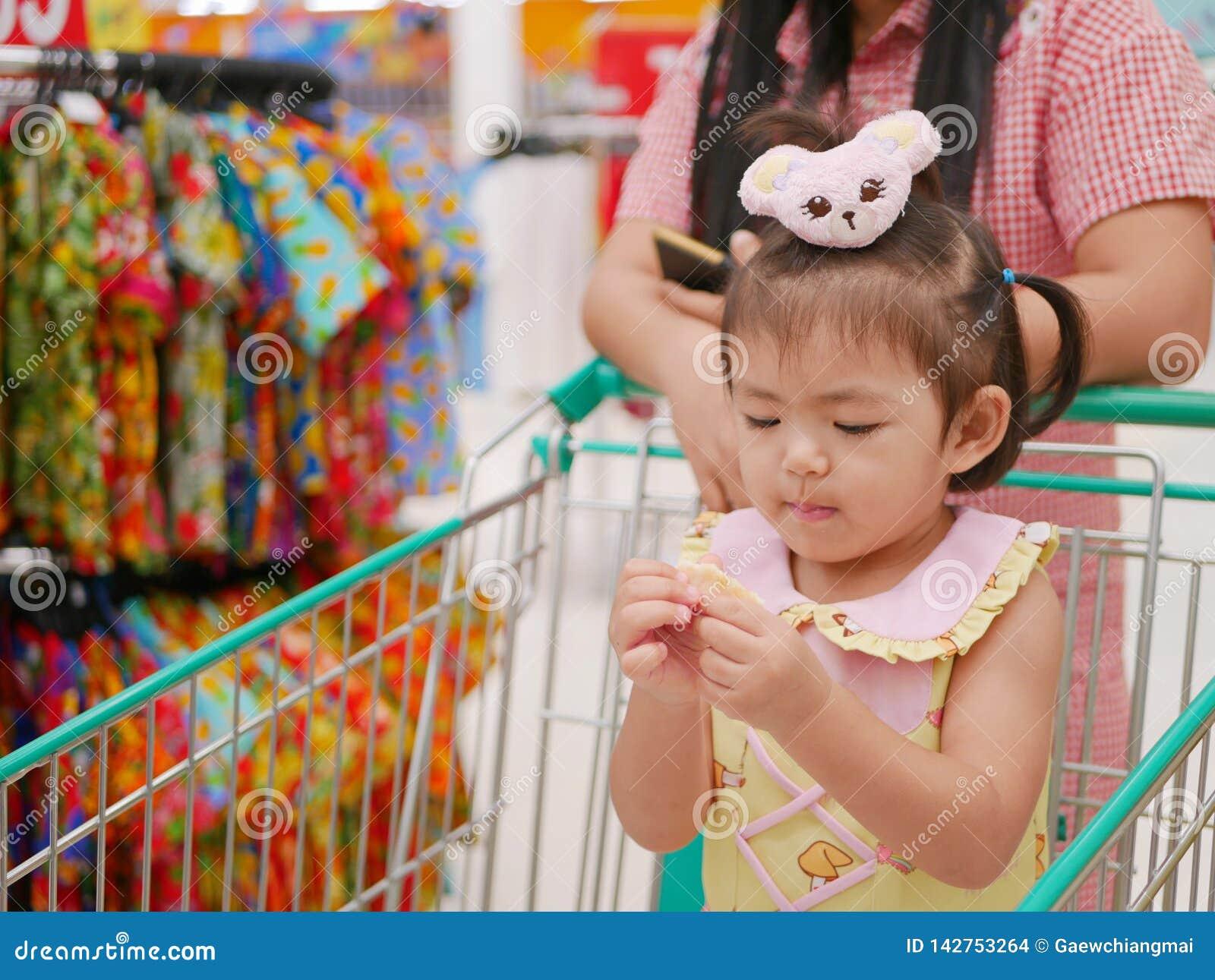 Weinig Aziatisch babymeisje die snack eten en zich in een boodschappenwagentje bevinden terwijl haar moeder het winkelen in een w