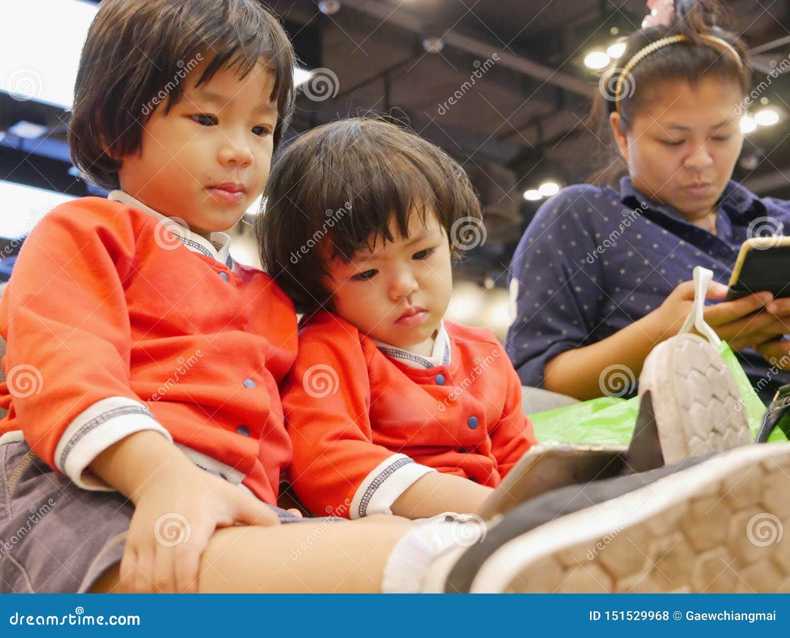 Weinig Aziatisch babymeisje, samen met haar jongere zuster, die op een smartphone, een zelfde zoals haar mamma, een zitting en ee