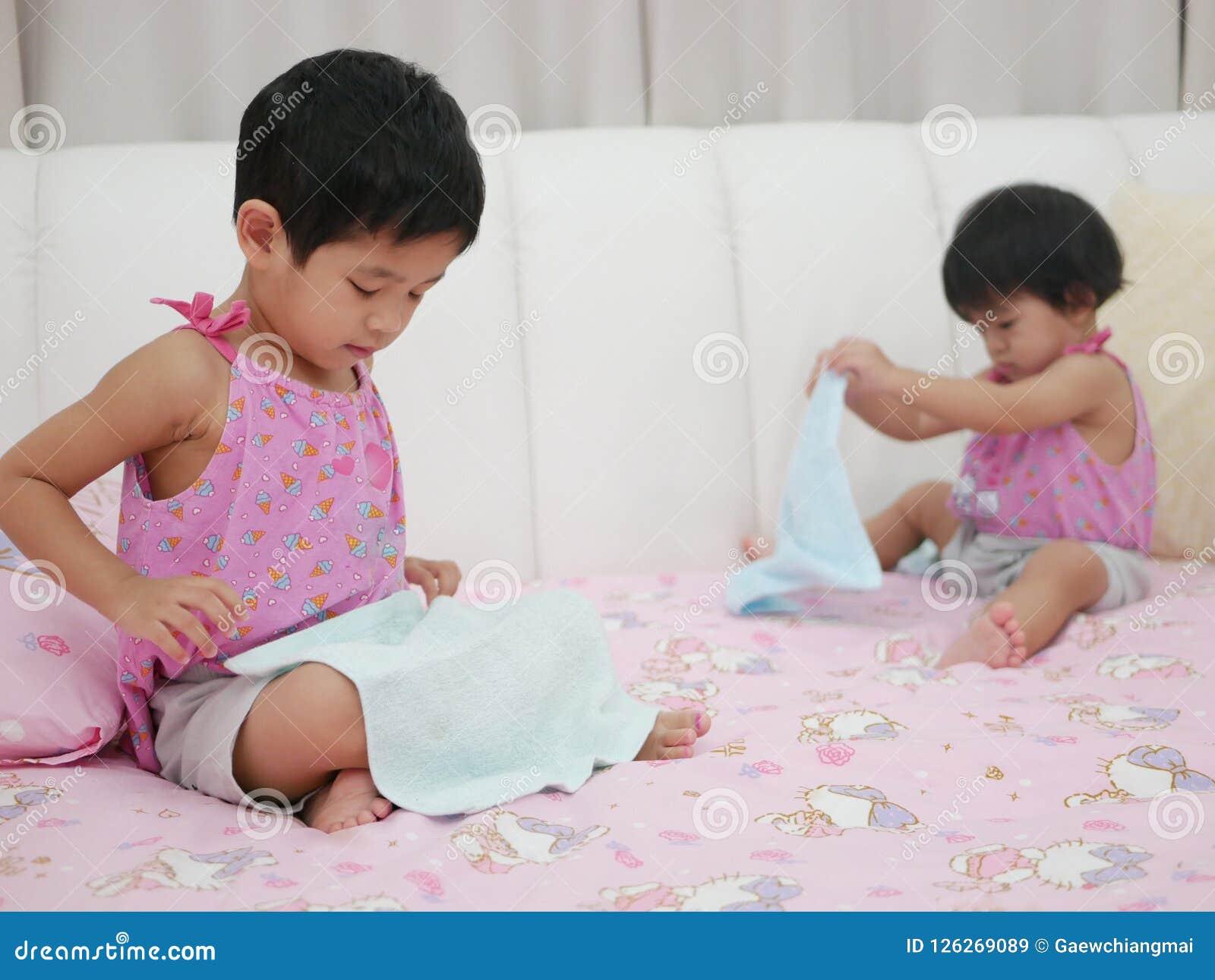 Weinig Aziatisch babymeisje verliet het leren om kleren te vouwen