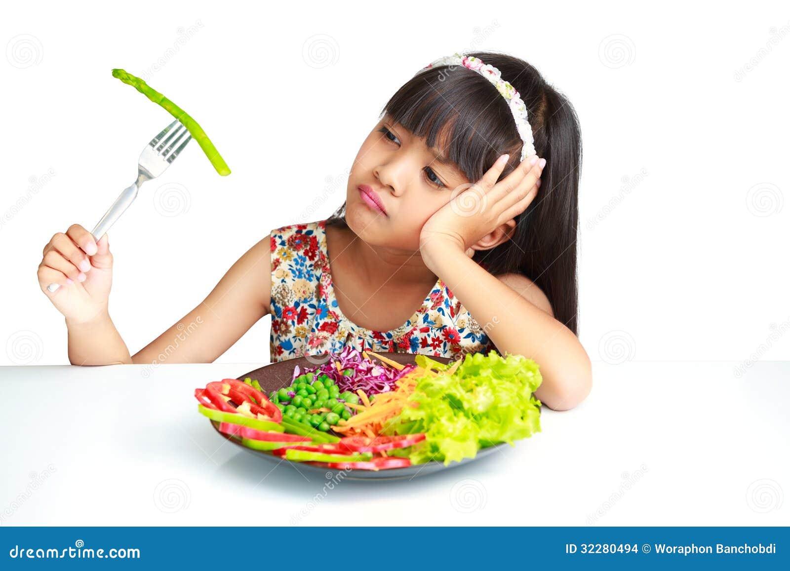Weinig Aziatisch meisje met uitdrukking van afschuw tegen broccoli