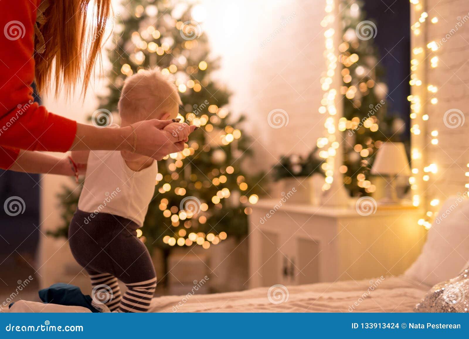 Weinig babyjongen 1 éénjarige die leren hoe te in een verfraaid Nieuwjaarhuis te lopen Mammagreep door de handen van haar zoon