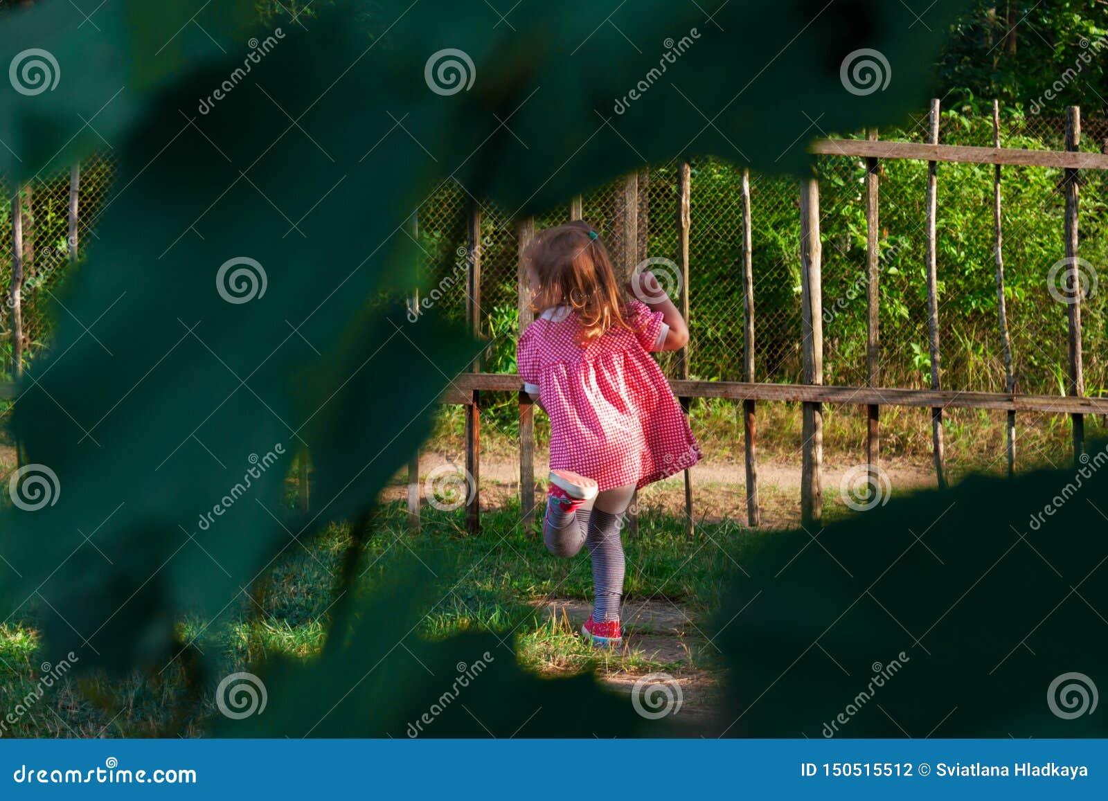 Weinig babymeisje die in de yard dichtbij het huis spelen