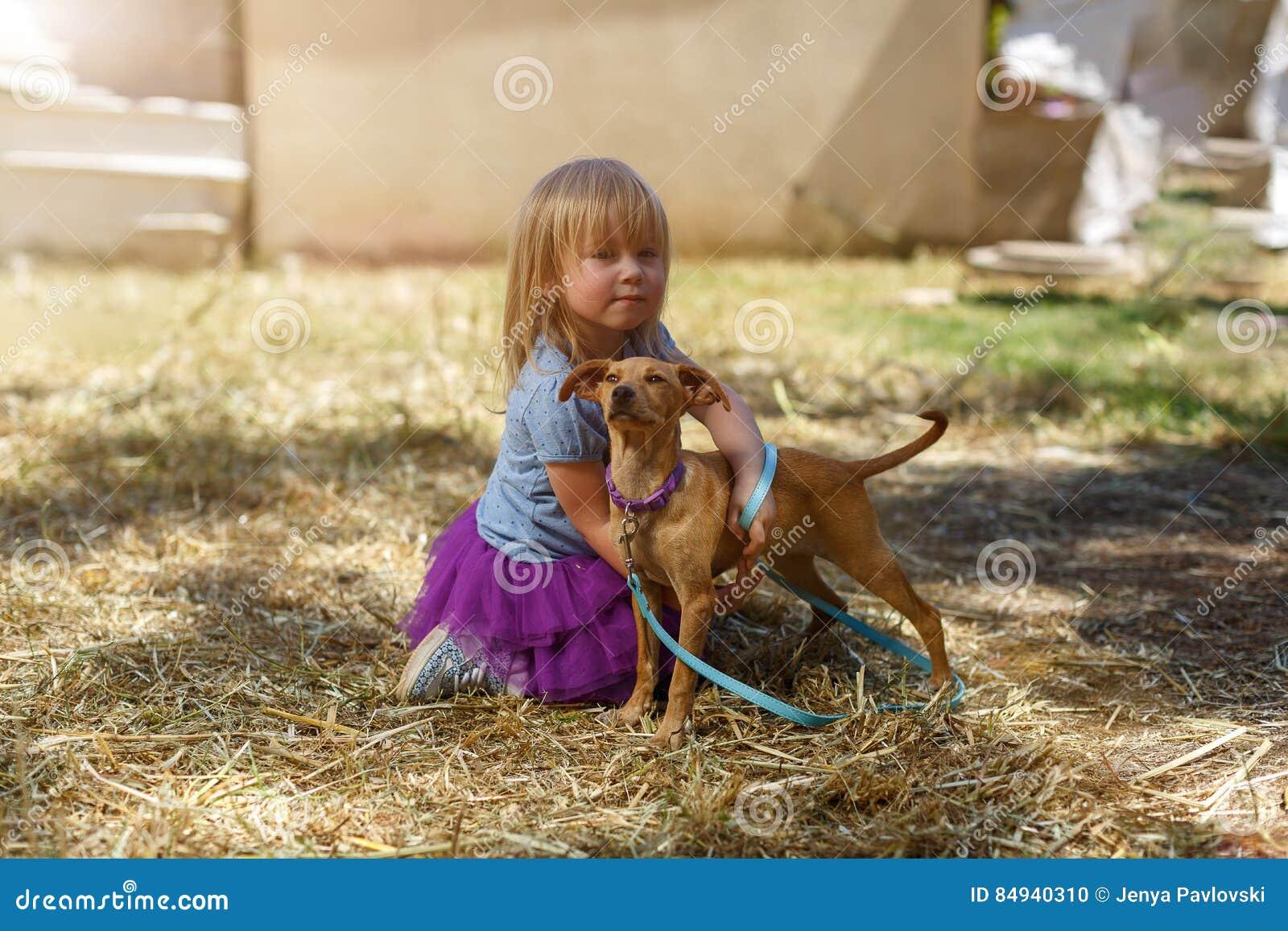 Weinig blond meisje met haar retrieverhond
