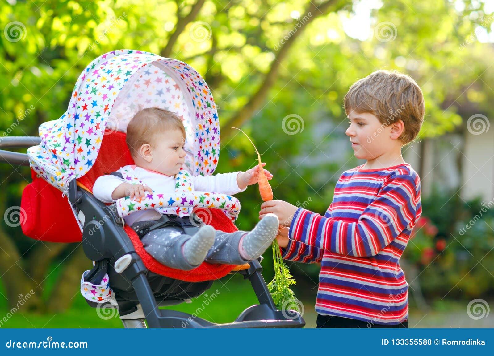 Weinig blonde jong geitjejongen die een wortel geven aan babyzuster Gelukkige siblings die gezonde snack eten De zitting van het