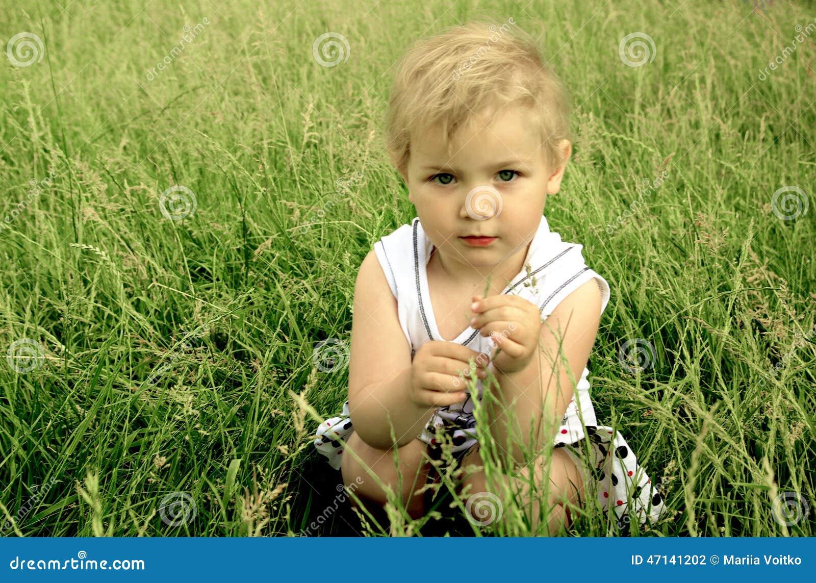 Weinig blonde meisjeszitting in het groene gras