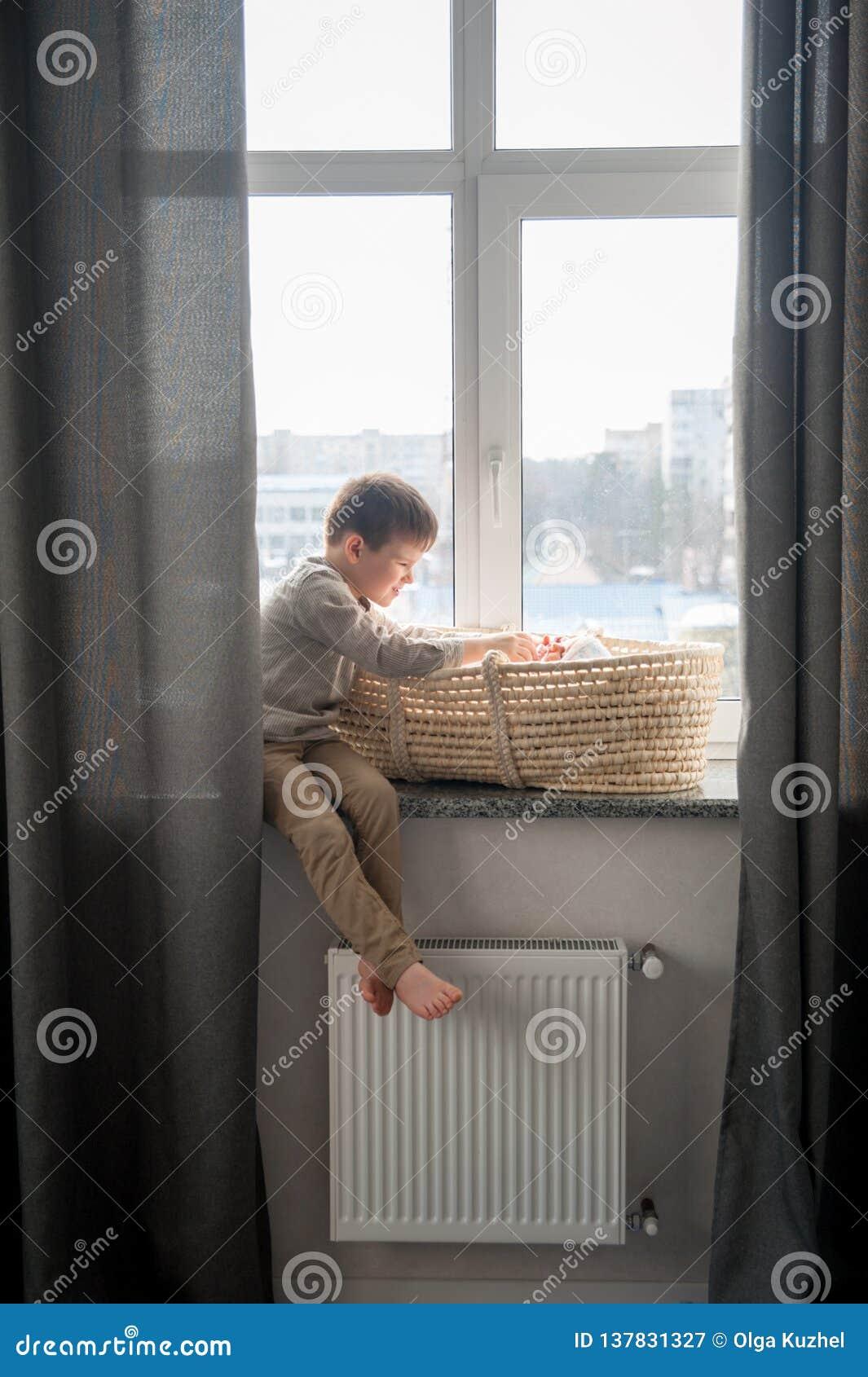 Weinig broer zit dichtbij het venster met himnewbornzuster in de wieg Kinderen met klein leeftijdsverschil