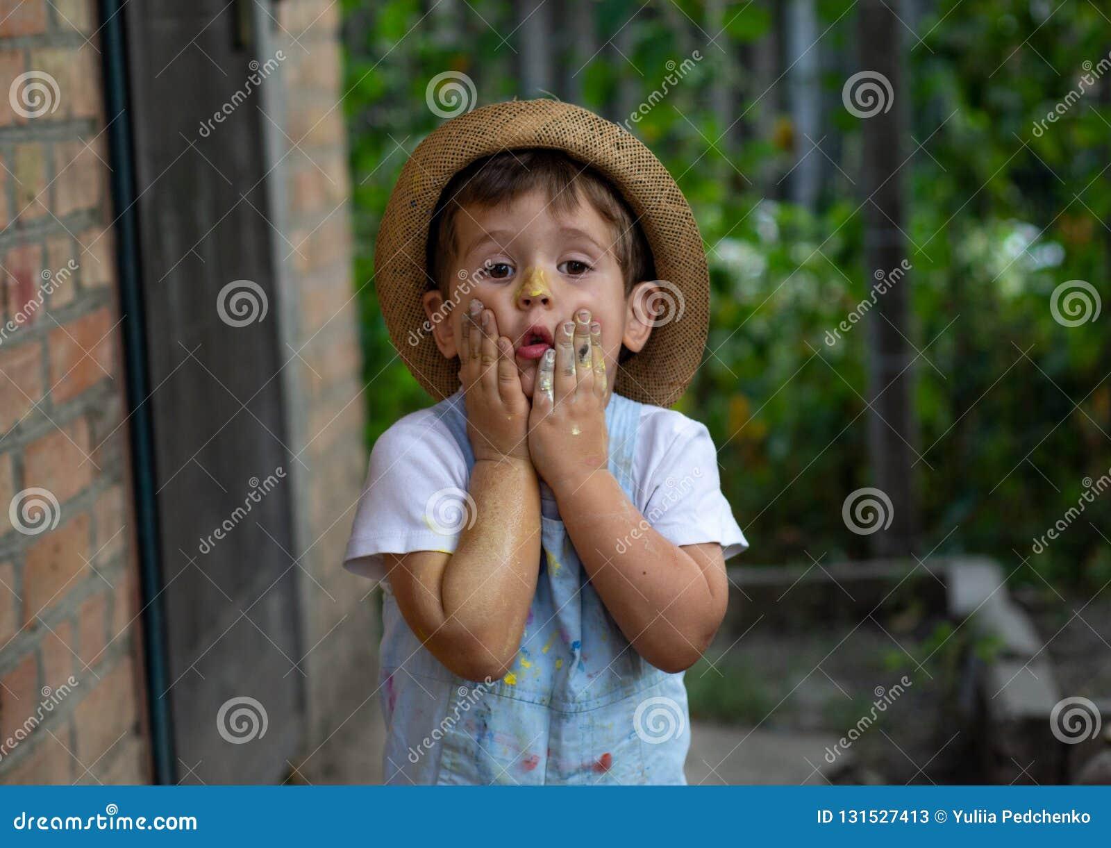 Weinig die jongenshanden in kleurrijke verven worden geschilderd Gelukkig jong geitje die pret hebben in openlucht