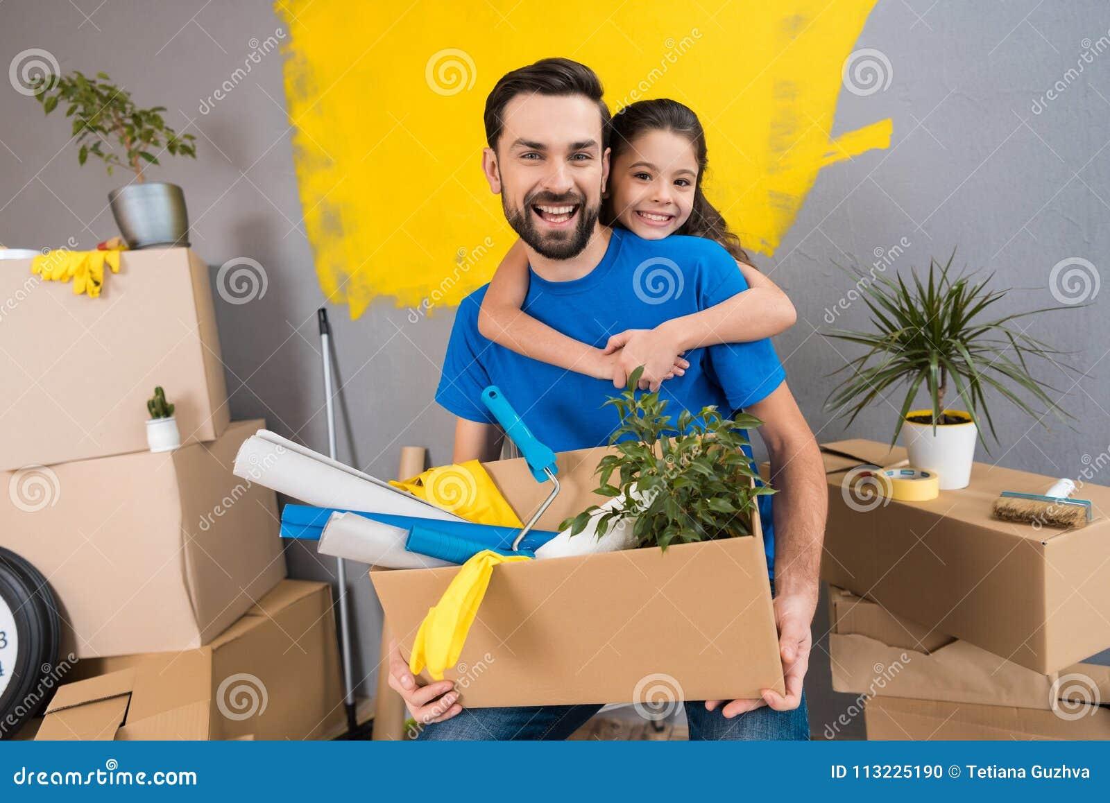 Weinig dochter koestert haar vader, die doos van hulpmiddelen en dingen houdt De familie huisvest samen reparaties