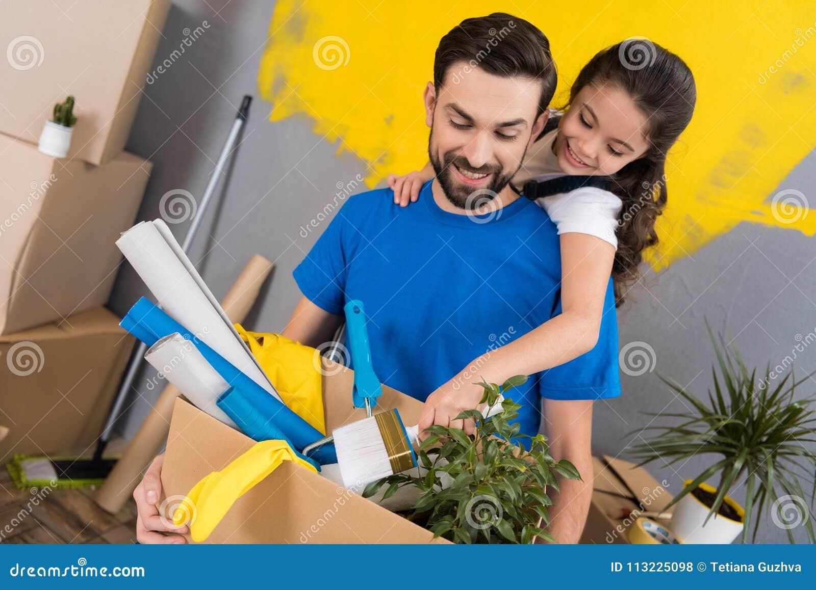 Weinig dochter met penseel koestert vader, die doos van hulpmiddelen en dingen houdt