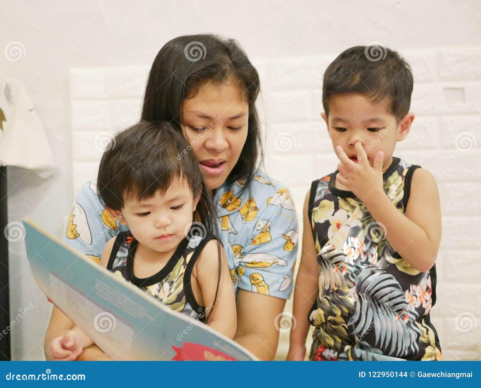 Weinig genieten van de Aziatische babymeisjes hebbend hun moeder die een boek lezen hardop aan hen