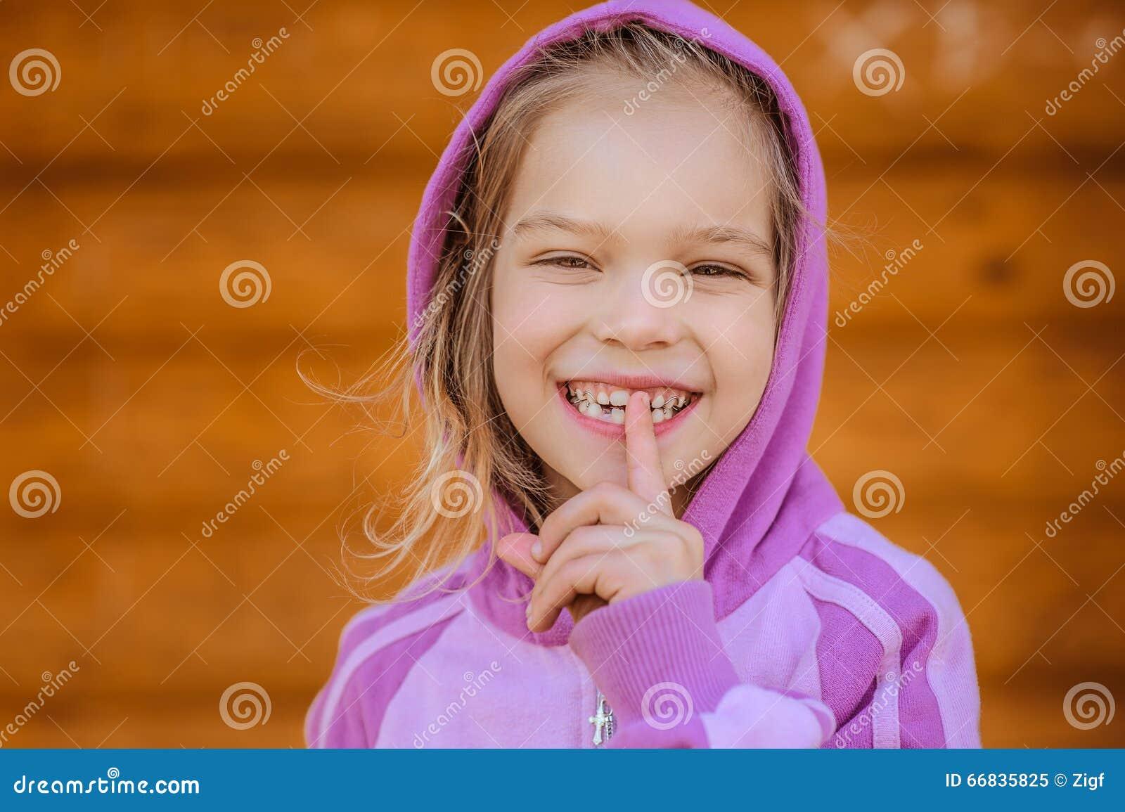 Weinig glimlachend meisje brengt wijsvinger aan lippen aan