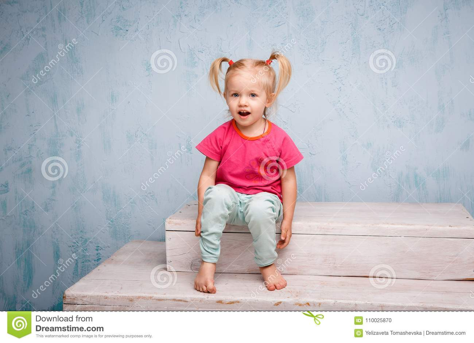 Weinig grappig blauw-eyed blonde van het meisjeskind met een kapsel twee paardestaarten op haar hoofdzitting op een roddel op de