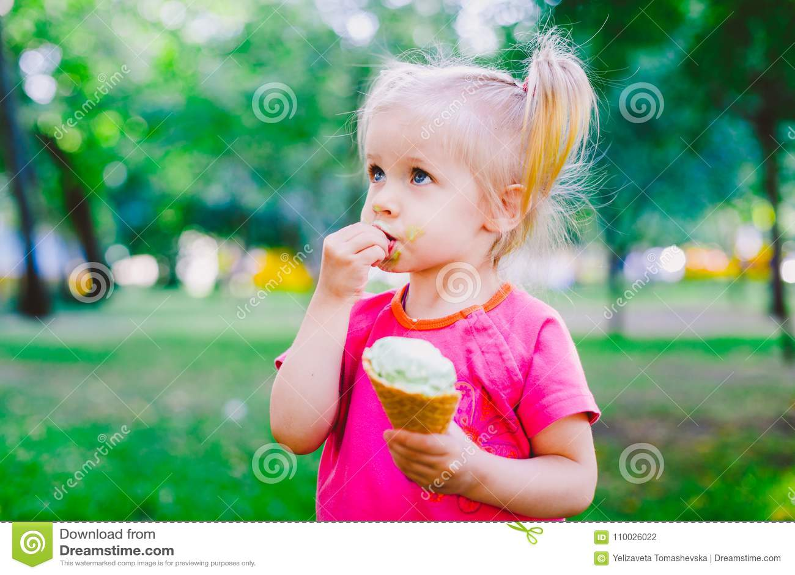 Weinig grappig meisjesblonde die zoet blauw roomijs in een wafelkop eten op een groene de zomerachtergrond in het park smeerde ha