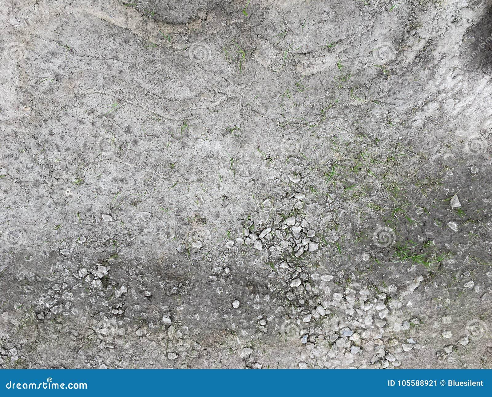 Weinig gras het groeien op de oppervlakte van barstende betonweg