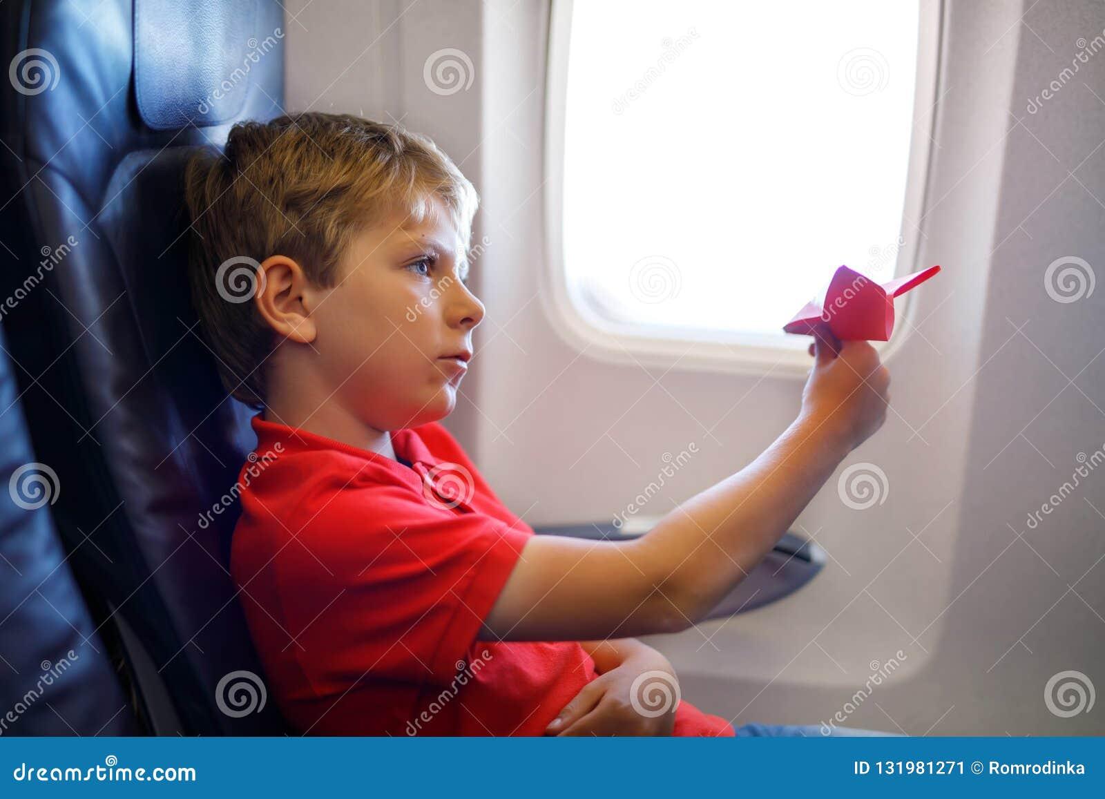 Weinig jong geitjejongen die met rood document vliegtuig tijdens vlucht op vliegtuig spelen Kindzitting binnen vliegtuigen door e