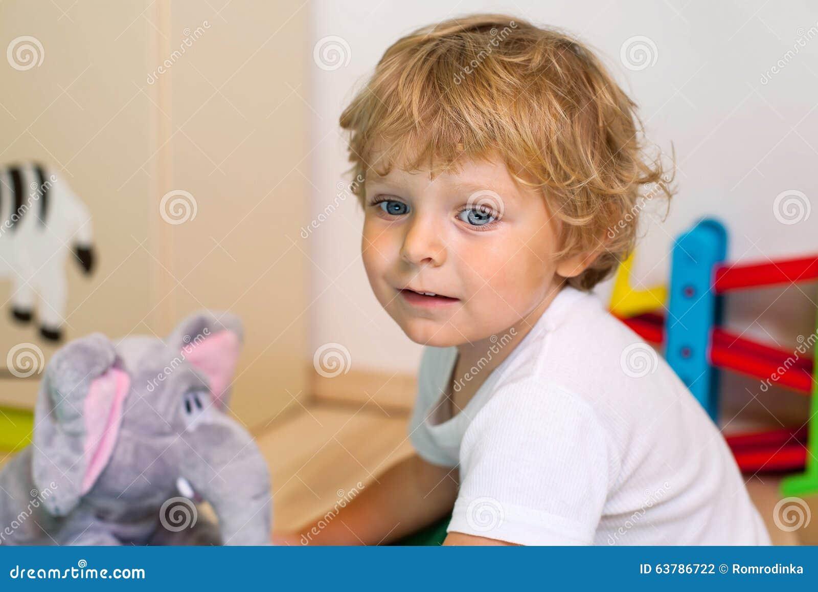 Weinig jong geitjejongen die met veel kleurrijk speelgoed spelen binnen