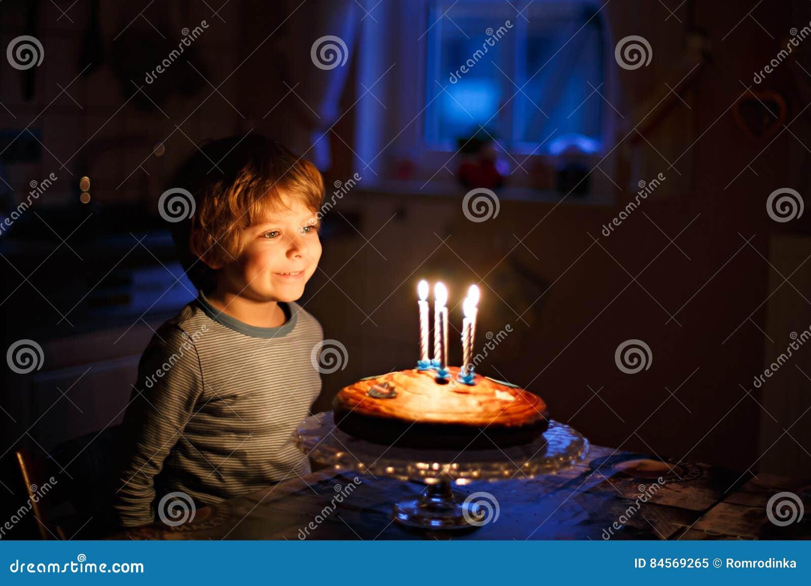 Weinig jong geitjejongen die zijn verjaardag vieren en kaarsen op cake blazen