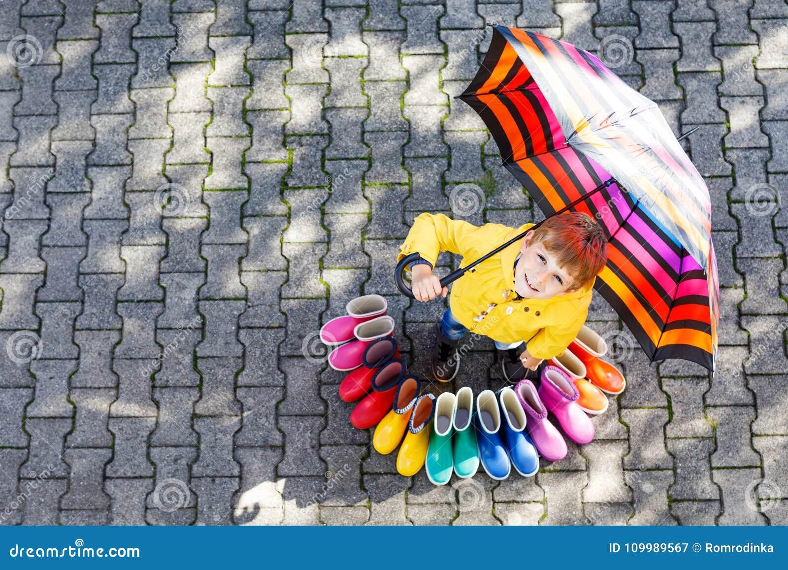 Weinig jong geitjejongen en groep kleurrijke regenlaarzen Blond kind die zich onder paraplu bevinden