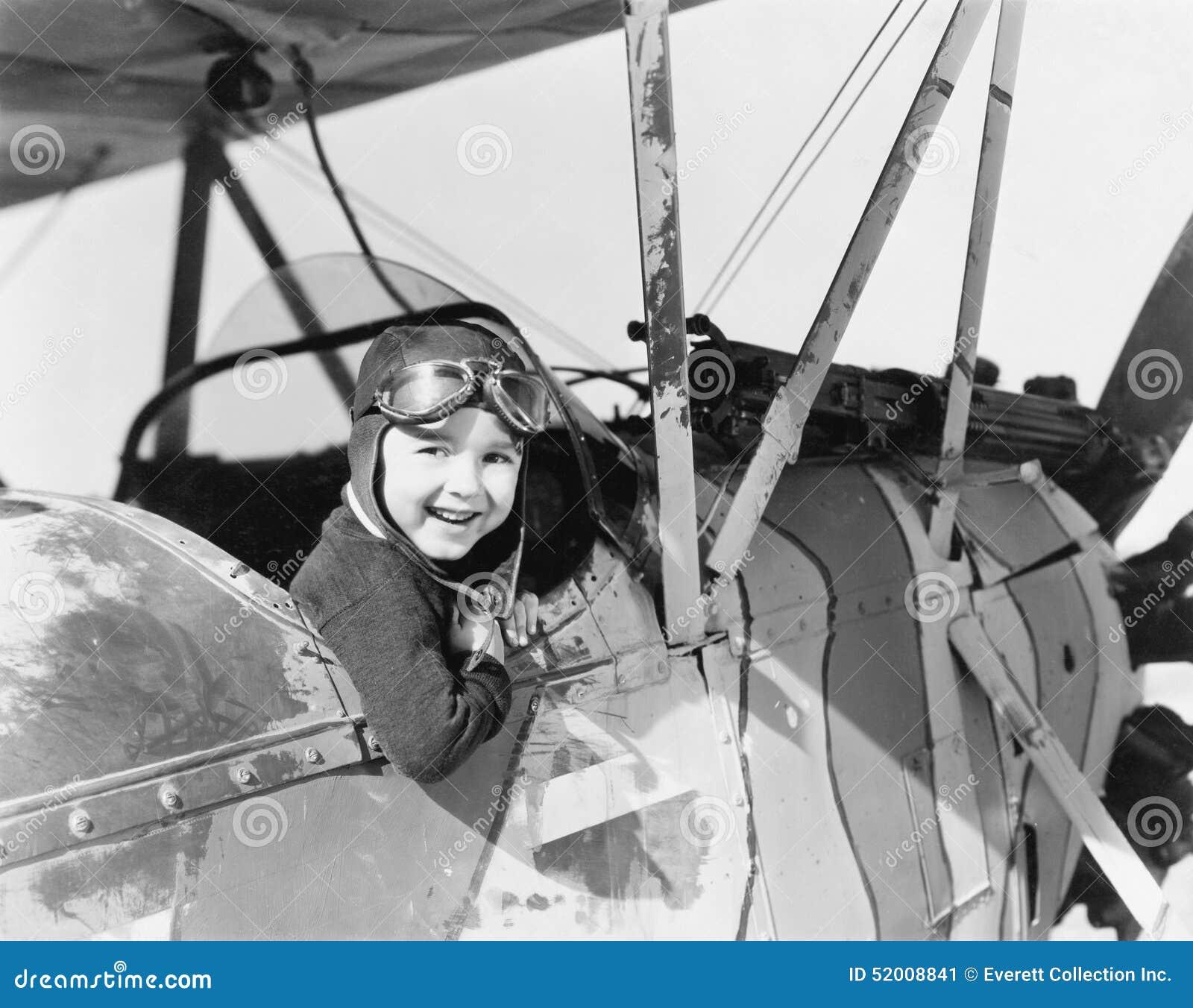 Weinig jongen in cockpit van vliegtuig (Alle afgeschilderde personen leven niet langer en geen landgoed bestaat Leveranciersgaran