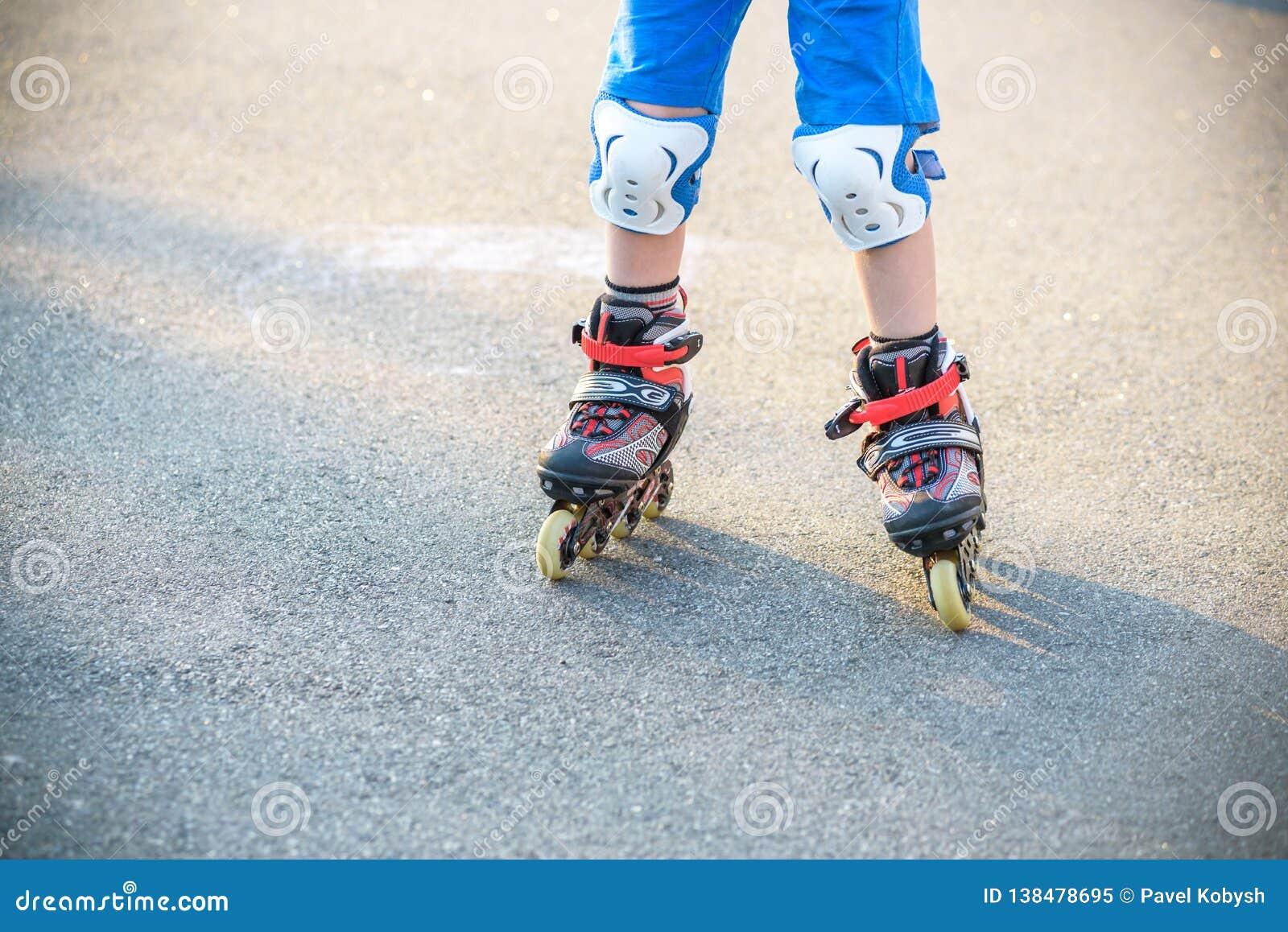 Weinig jongen die aan rolschaats in de zomerpark leren Kinderen die beschermingsstootkussens voor veilige rol het schaatsen rit d