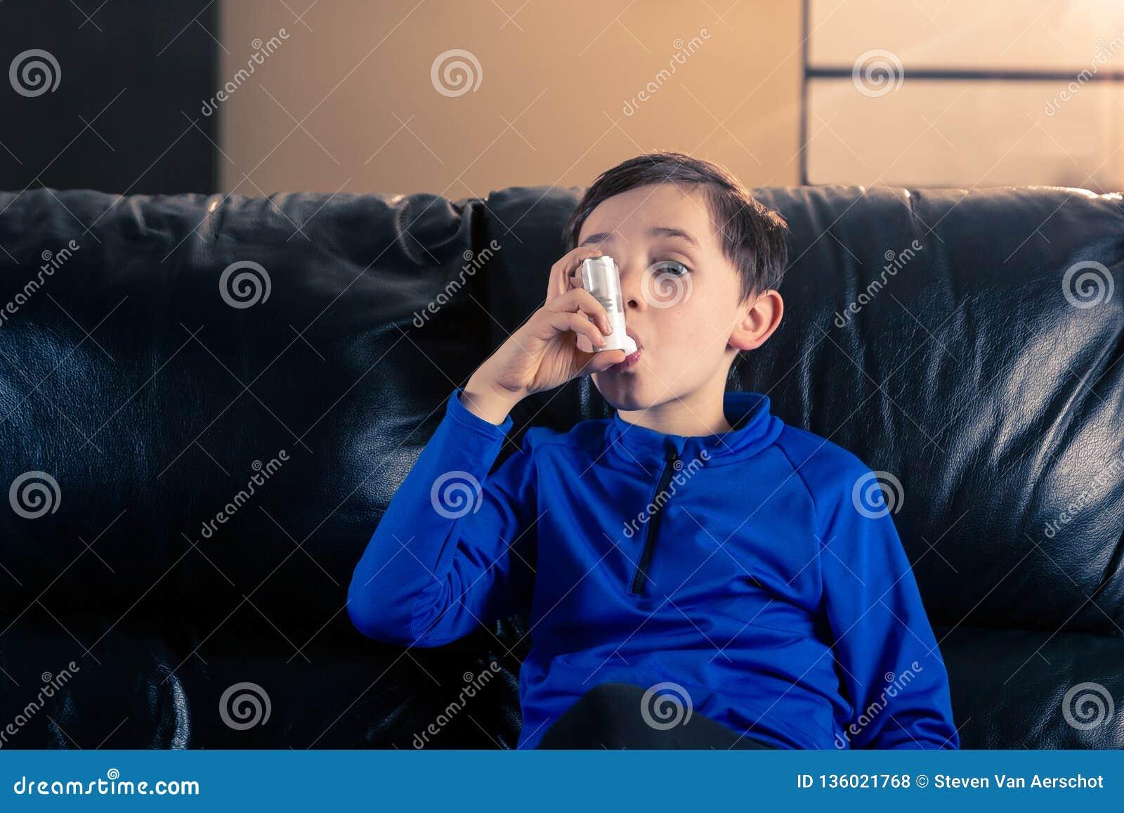 Weinig jongen die een astmainhaleertoestel binnen met behulp van